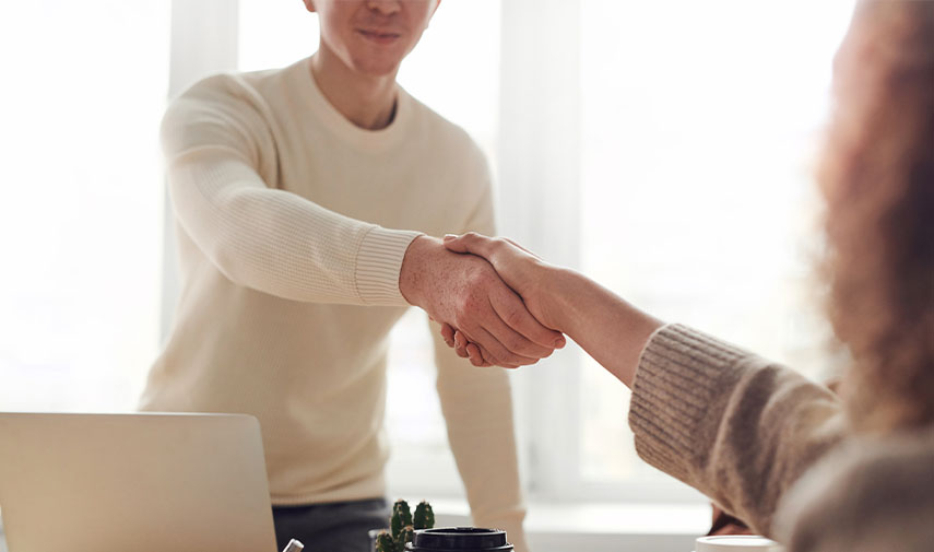 Man with job search anxiety shaking woman's hand in interview